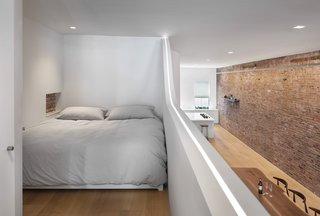 The cozy sleeping area fits a king-sized bed and houses a hidden television. A nightstand is incorporated into a recess in the plaster walls, showcasing exposed brick.