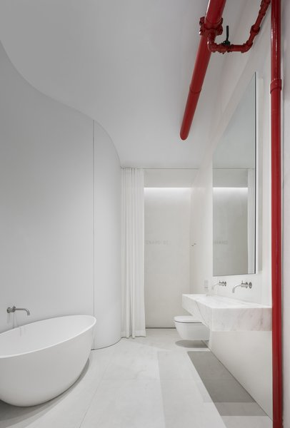 "The bathroom continues the same all-white and marble palette set by the rest of the apartment, particularly the kitchen. The trough sink seems to float mid-air, and the organic shape of the freestanding bathtub is reflected in the curve of the wall. A bright red sprinkler main valve adds a pop of color. In the shower, a custom mosaic spelling ""Grand St."" composed of 1/2"" thick Thassos stone blocks shines subtly against the waterproof plaster wall."