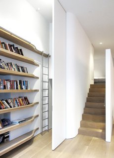 The stainless-steel ladder telescopes up and down and is a custom piece that travels along a curved track, imitating the form of the curved solid oak shelving. When pushed behind the sleeping loft to the laundry area, it is out of sight.