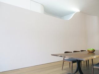 The top of the mezzanine wall peels away, allowing the space to remain somewhat open. It also provides an opportunity to inset a flush, recessed, flexible LED light into the top of the wall as it dies into the ceiling.