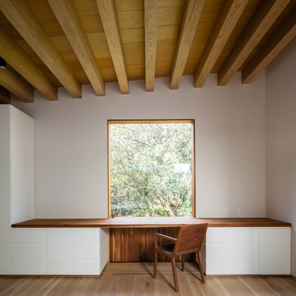 An upstairs office features built-in millwork and a wood-topped desk, with plenty of surface and storage area. A window is carefully placed in front of the desk for natural light and views.
