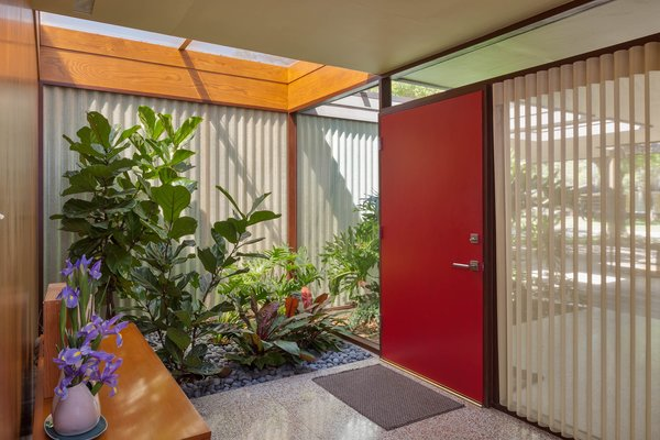 The entryway of the home is characterized not only by the red front door, but also by the large panels of glass on either side, including one that almost disappears, allowing the planting box to appear to continue seamlessly into the interior.