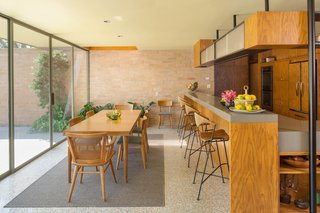 """The kitchen opens directly onto the dining room; the 1954 article in Good Housekeeping noted that the dining room was separated from the walled garden by large sliding glass doors, """"uniting indoors and out."""""""