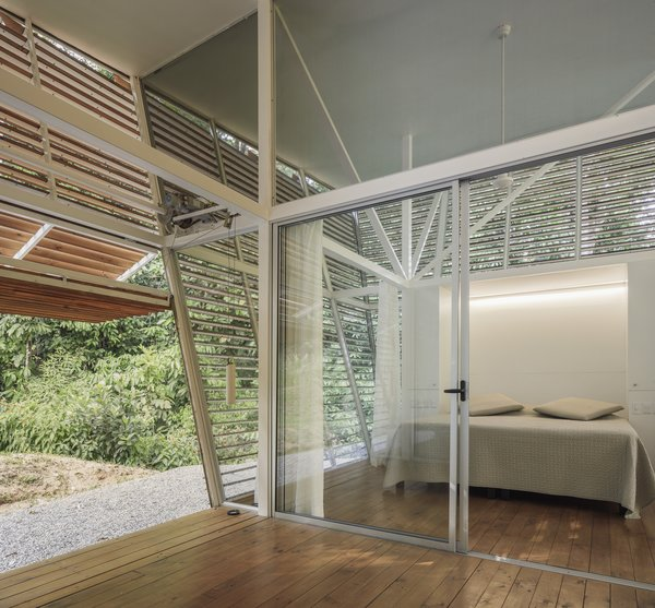 The secondary, internal facade of glass can be opened and closed with large sliding glass doors. Bedrooms contain minimal furniture that is produced as prefabricated sections that are then inserted into the frame created by the steel structure.