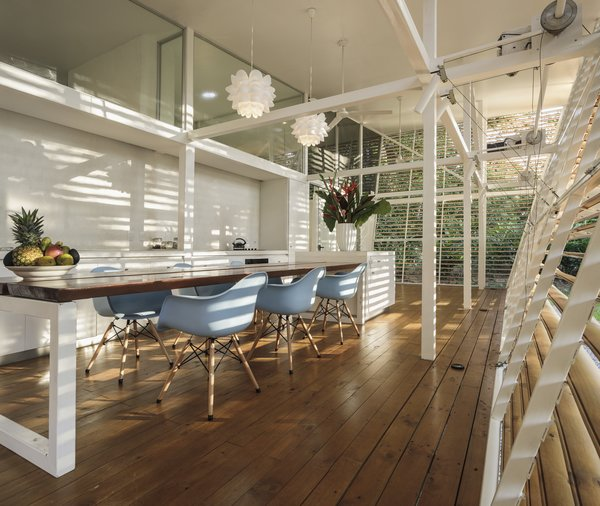 The open kitchen has an attached dining table, and is located outside of the secondary glass facade enclosure. This allows not only for natural ventilation while cooking, but also views to the greenery beyond.