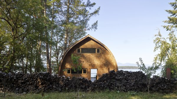 The rear of the home faces the forest, and a wall of firewood creates a sense of seclusion. Operable windows allow for passive ventilation on the upper and lower floors.