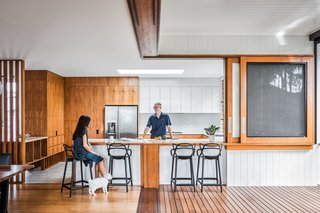 The light-filled kitchen opens onto the indoor/outdoor area of the porch and features white and wood cabinets.