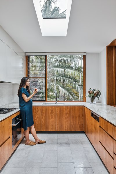 Louvered windows in the kitchen and bathroom provide natural ventilation. The floor and countertop have a natural, organic texture to them that ensures the space feels homey and modern rather than cold and clinical.