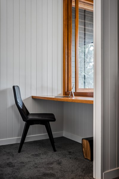 The master bedroom has a small study, outfitted with a wood countertop that matches the wood window and frame.
