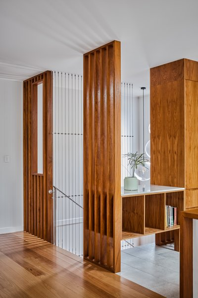 Vertical wood elements surrounding the staircase are emphasized by cables that stretch down to the lower level.