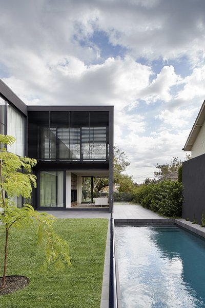 The U-shaped home wraps around a central garden space with an adjacent pool; floor-to-ceiling sliding glass doors create a seamless transition from indoors to out.