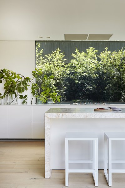 Both windows and doors in the kitchen provide views of greenery. The kitchen island features the stone that inspired the color palette for the rest of the home's interior.