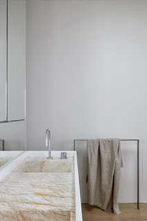 The bathroom features the same stone as the kitchen countertops, providing visual interest in the otherwise white bathroom.