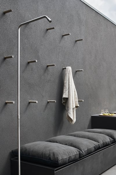 An outdoor shower by the pool has a minimalist faucet with simple, metal, peg-like hooks for hanging towels.