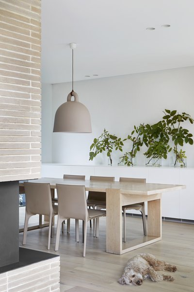 A bell-shaped pendant hangs over the dining table, continuing the warm taupes and beiges found in the double-sided fireplace and wood table and floors.