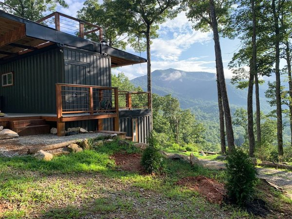 Nestled in the hills of the Smoky Mountains and oriented to prioritize views of the Appalachian Trail, this prefab cabin is constructed out of three shipping containers topped with a generous, double-sided overhang that creates two porches. The upper-level shipping container is available for vacation rentals on Airbnb.