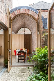 The new addition extends into the backyard, which has been transformed into a small courtyard that draws light into the interior.