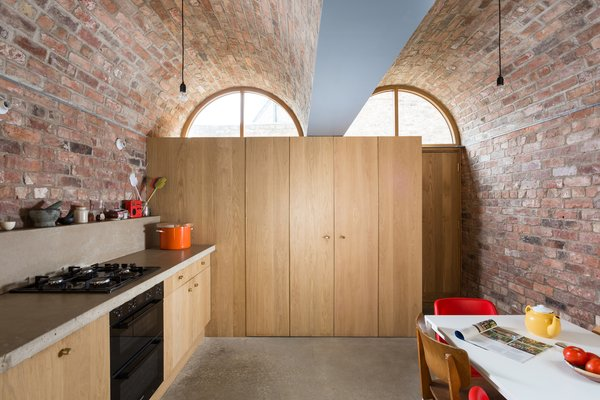 Inspired by the textured brick in the adjacent properties in the neighborhood, a Victorian terrace house in Northeast England is updated with an addition that mirrors the surrounding architecture. Using the same local, handmade brick already in the home, Studio Ben Allen set out to convert the rear of the house into an airy work, dining, and storage space that fused seamlessly with the existing home. However, the addition also received a distinguishing characteristic—an arched, load-bearing roof.