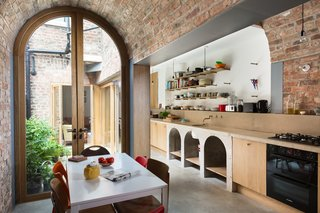 The warm textures and tones of the exterior are continued on the interior, where the brick walls are left exposed in certain areas. The poured-in-place concrete arches under the sink echo the arched doorways and barrel-vaulted ceilings.