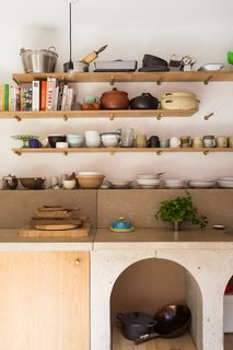 The use of concrete and wood shelving and cabinets continue the texture and warmth of the brick, but in different tones and scales.