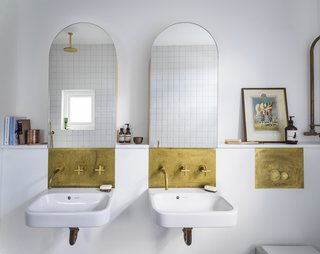 Even the renovated bathrooms maintain the arched motif with arched mirrors above solid, uncoated brass hardware that will patina over time.