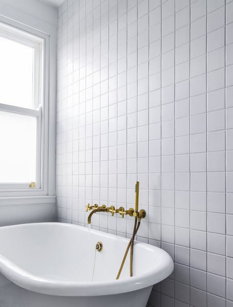 The bath fixtures received a similar treatment of uncoated brass that gleams against a backdrop of white tile.