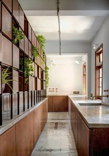The service corridor emphasizes axial circulation and austerity of materials, with concrete countertops and wood cabinetry.