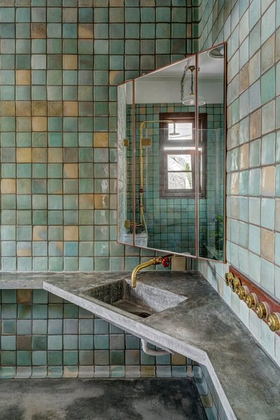 The guest bathroom continues the concrete countertops seen in the kitchen, but paired with handmade tiles that range in tone from green to yellow.