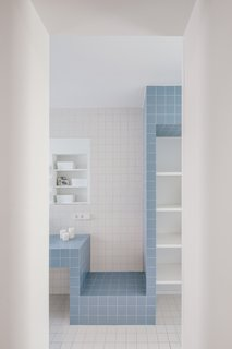 """In the bathrooms, the oak flooring is replaced by ceramic tile, which covers floors and walls,"" explain the architects. The colors of the square tiles changes depending on the bathroom, but remain simple and straightforward."