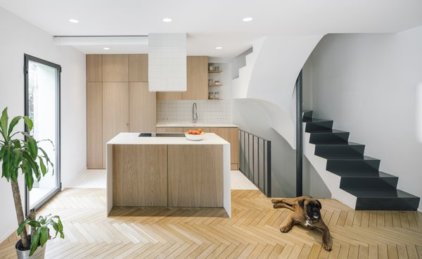 The kitchen's white oak cabinetry and island riff off the oak flooring in the rest of the house. By contrast, the floor, countertops, and hood are all white.
