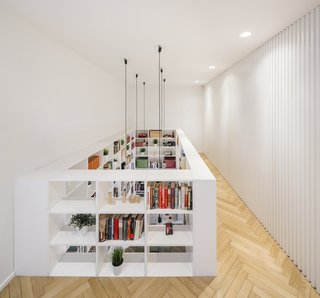On the second floor, wood slats along one wall conceal doors to two bedrooms, while the open shelving acts as both storage and a handrail for the double-height living room below.