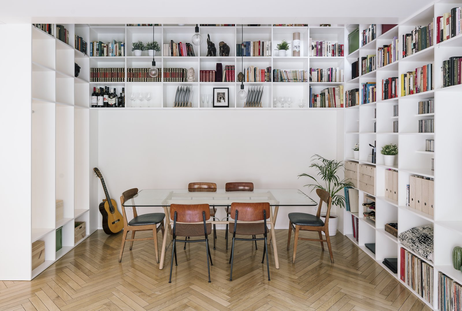 6House by Zooco Estudio double-height dining room with wraparound white bookshelves