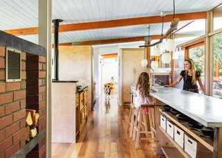 Kasey and Nick chose to keep the long, reclaimed-marble countertop in the kitchen, which had been renovated by the previous owners of the 1954 Wendell Lovett home.