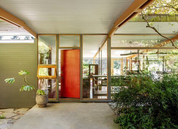 As you approach the Hilltop House from the covered breezeway that adjoins the garage, it is possible to see through the carefully placed windows to the greenery on the home's other side.