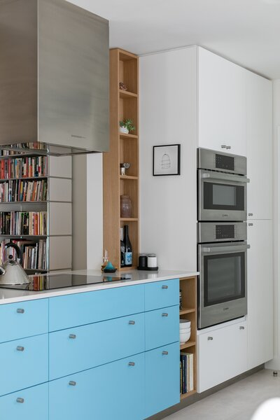 The new appliances, hardware, and toe kick of the cabinetry are all of brushed aluminum, tying back to the home's midcentury window aluminum frames.