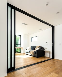 Sliding doors inspired by Japanese shoji screens can close off the office, which doubles as a guest room, for privacy.