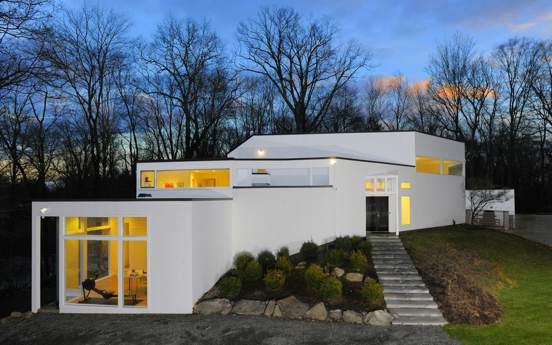 Designed by Anthony Wooiner, this striking residence in New York's northern suburbs blurs the line between indoors and out, flanked by dramatic glass walls that embrace the home's natural surroundings. It now awaits its next residents.  Hycliff House