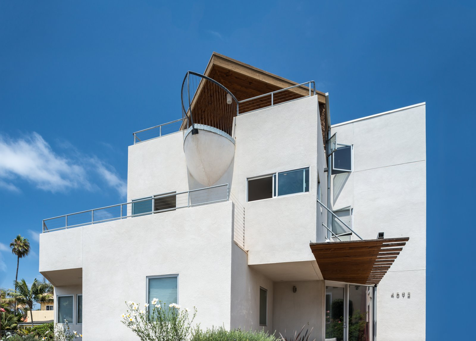 Three stories of ocean views, and a unique boat-bow balcony offers a bit of humor to this beachy neighborhood.  Photo 10 of 11 in Slim Is in For These 10 Skinny Homes from The Beach House