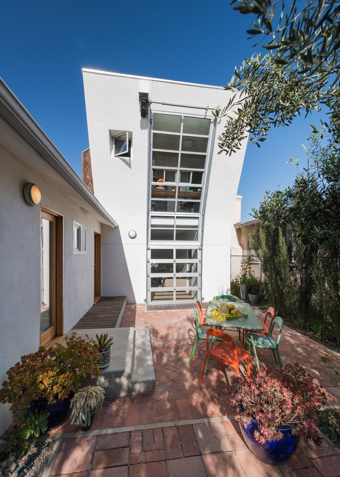 The two story addition looks into the back yard from the playroom and upstairs office. The entire curved wall opens up with a motorized garage-door window.  Photo 7 of 12 in 11 Modern Ranch-Style Homes from The Ranch House