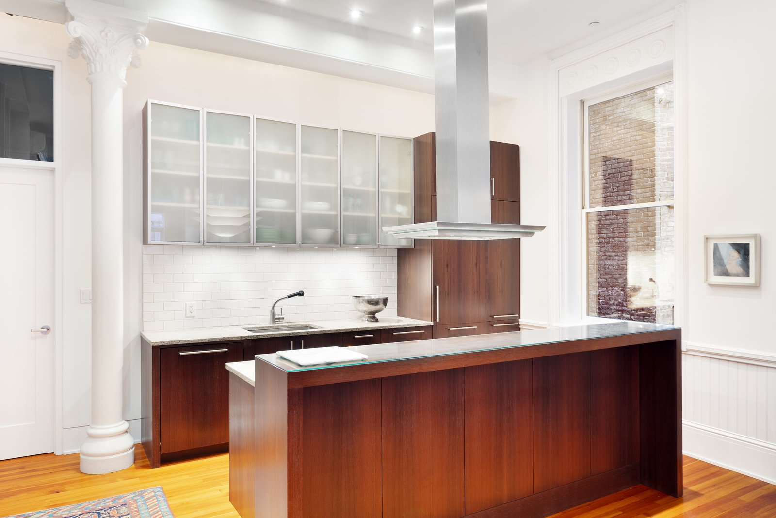 Kitchen, Wall Oven, Refrigerator, and Medium Hardwood Floor The home possesses an open windowed kitchen with large island, custom cabinetry, stainless steel appliances, and a large breakfast bar - an entertaining dream.  Renovated Co-op in Historic Astor Memorial School