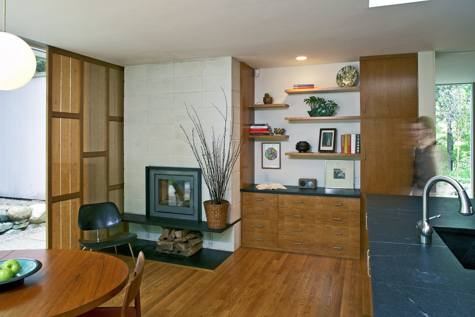 A view of the kitchen addition with its Rais fireplace unit, veneer sunscreen, and custom cabinets and shelves.  Giese House by Wolf Architects, Inc.