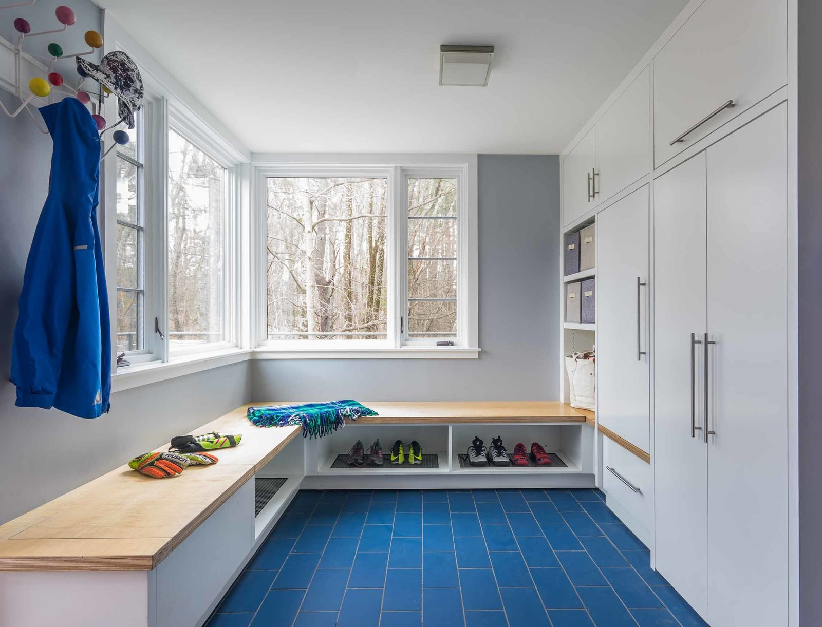 Laundry, Concealed, White, and Wood Maple veneer ApplePly tops this bench in the new mudroom, which provides boot and shoe storage/drainage, while other cabinets conceal a variety of storage spaces.   Best Laundry Photos from Historic Modern Expansion