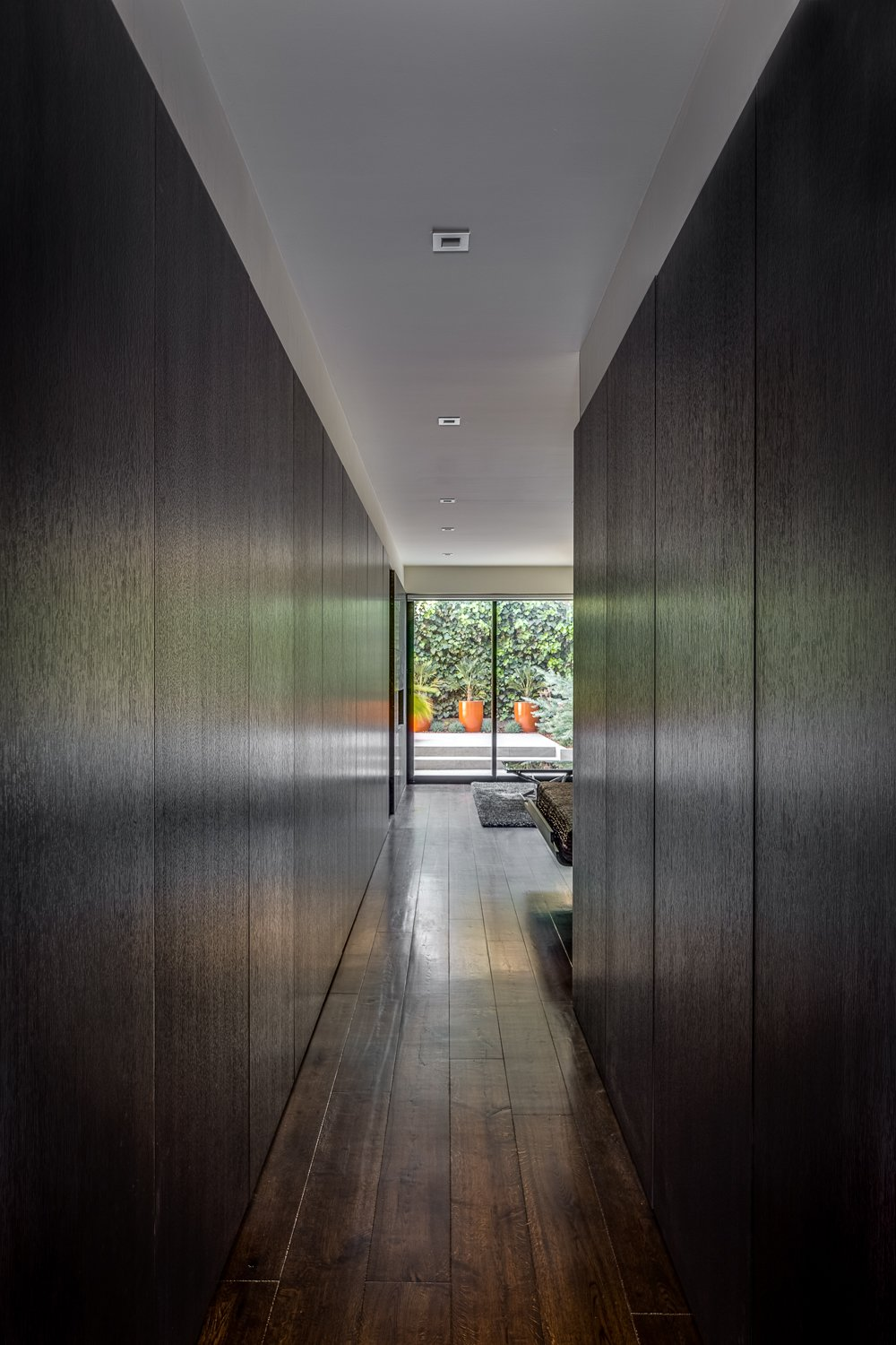 Hallway and Dark Hardwood Floor Panels Covering Closets and Storage - Master Suite - Rift-cut white oak, full-height, honeycomb panels and doors: hand wire brushed, stained, sealed, sanded, glazed, sanded and top-coate  Castro Residence by Diego Pacheco Design Practice