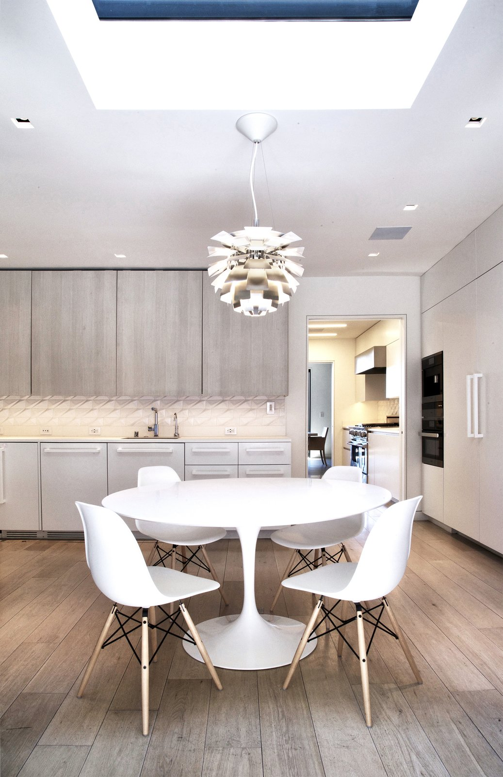 Breakfast Room - Saarinen Tulip Table, Eames side chairs, Miele appliances, Louis Poulsen PH Stainless Steel Artichoke light  Lyon Residence by Diego Pacheco Design Practice