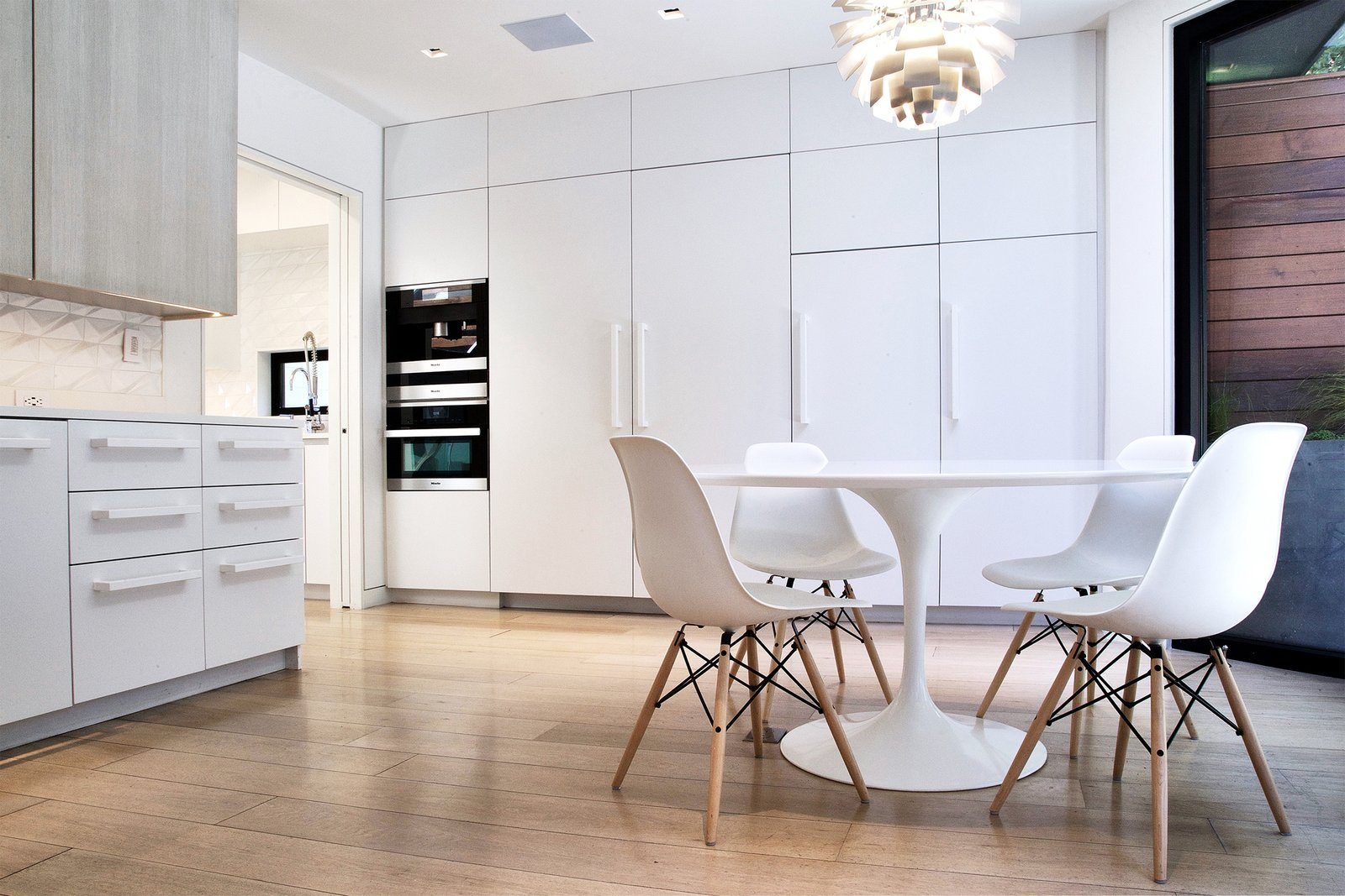 Breakfast Room - Saarinen Tulip Table, Eames side chairs, Miele appliances, Louis Poulsen PH Stainless Steel Artichoke light Tagged: Dining Room, Chair, Table, Pendant Lighting, and Medium Hardwood Floor.  Lyon Residence by Diego Pacheco Design Practice