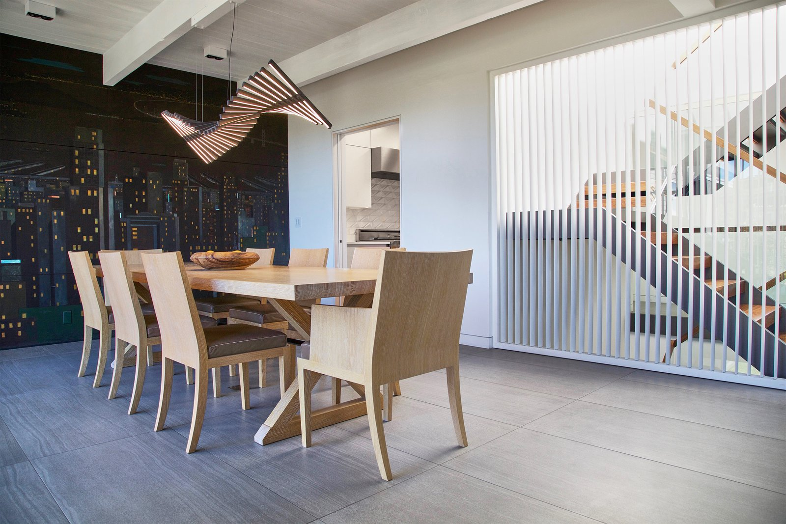 Dining Room, Chair, Table, Ceramic Tile Floor, Accent Lighting, and Track Lighting Dining Room - operable louvers at stair, original Jose Moya del Pino cityscape mural, Vibia Rythm light, Hermés table and chairs  Lyon Residence by Diego Pacheco Design Practice