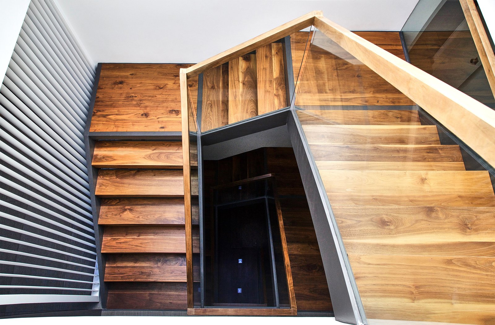 Staircase, Wood Railing, Wood Tread, and Glass Railing Walnut and Steel stair connecting all floors  Lyon Residence by Diego Pacheco Design Practice