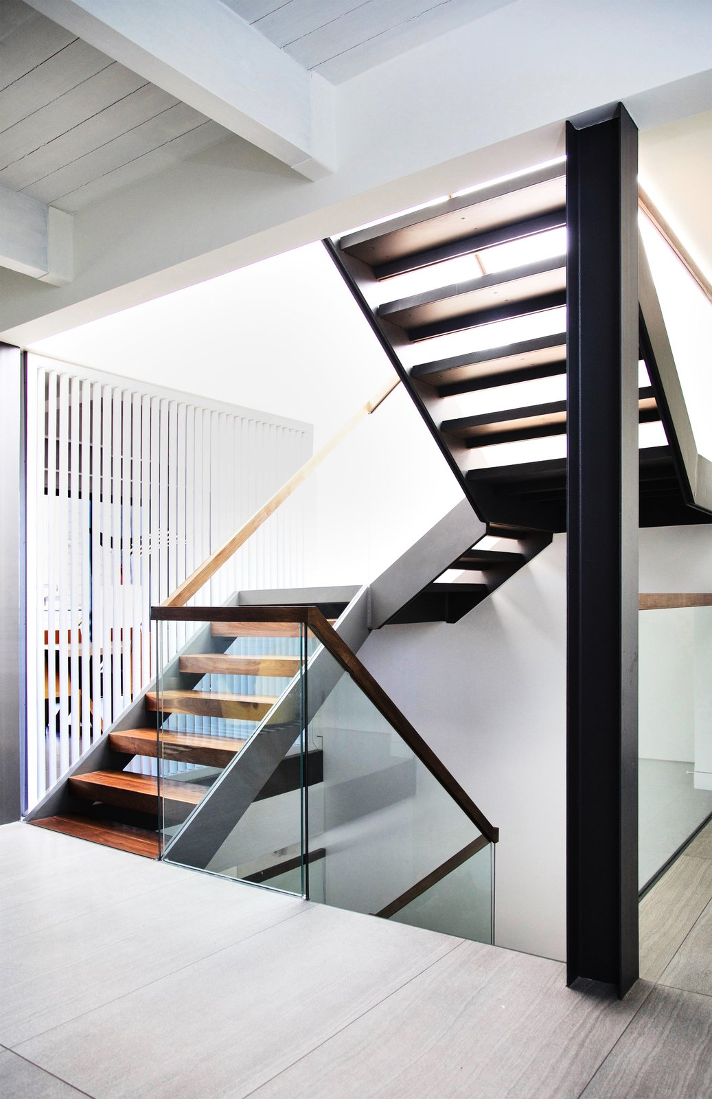 Staircase, Wood Tread, Wood Railing, and Glass Railing Walnut and Steel stair connecting all floors  Lyon Residence by Diego Pacheco Design Practice