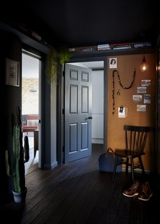 The entrance hall, with bamboo flooring, dark grey paintwork, and a cork wall for added texture.