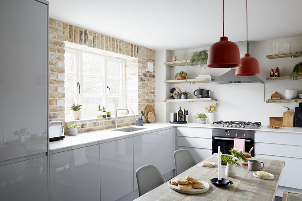 A brick wall and reclaimed timber shelves add character and warmth against the modern grey kitchen units.  Eames DSW dining chairs and pendant lights by Muuto bring colourful Scandi touches.